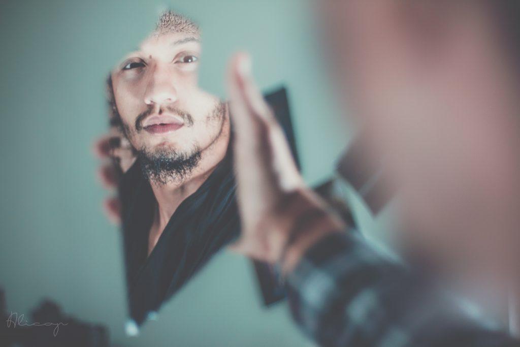 homme se regardant dans un miroir (2ème étape de la routine matinale : les affirmations positves)
