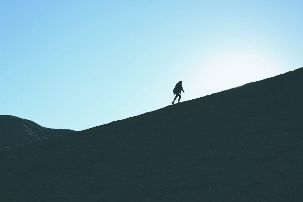 personne qui monte une montagne pour démontrer le fait de s'améliorer