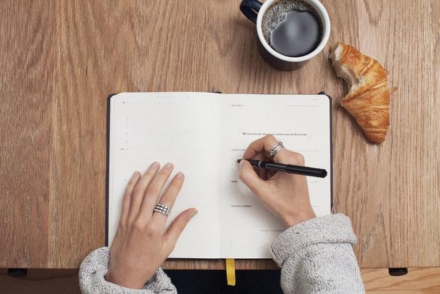 Femme qui écrit ses objectifs sur un journal