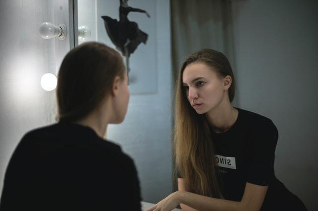 femme avec un t-shirt noir se regardant devant le miroir pour se répéter des affirmations positives