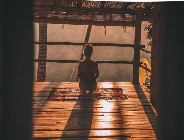 femme méditant le matin sur son balcon face au soleil