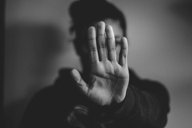 Femme faisant le signe stop avec sa main